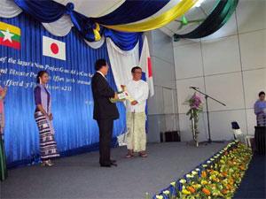 (写真) 沼田大使よりチョー・リン建設省統括部長にレプリカキーの贈呈 屋外でのレ... ミャンマ